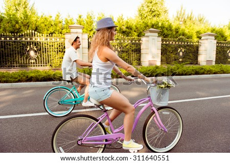 Happy young couple in love cycling race - stock photo