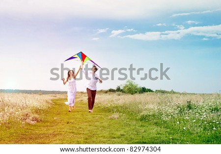 Happy young couple in love flying a kite - stock photo