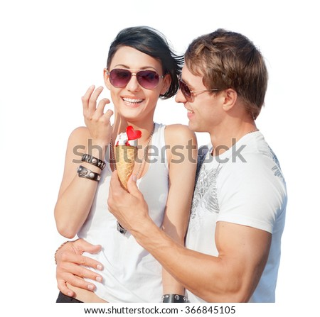 Happy young couple in love in sunglasses with ice-cream isolated on white background - stock photo