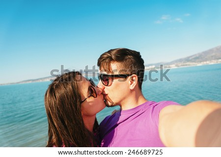 Happy young couple in love kissing and taking self-portrait on beach on background of blue sea - stock photo