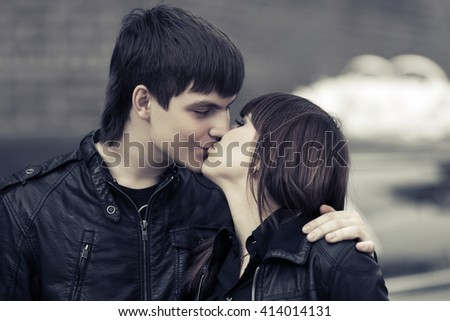Happy young couple in love kissing outdoor. Male and female fashion model in leather jackets