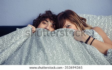 Happy young couple in love laughing and covering their mouths under a duvet. Love and couple relationships concept. - stock photo