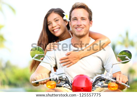 Happy young couple in love on scooter driving together. Multiracial couple having fun in the free outdoor. Smiling Caucasian man and Asian woman. - stock photo