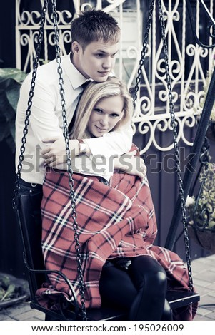 Happy young couple in love on the swing - stock photo