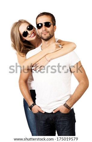 Happy young couple in love posing at studio. Isolated over white. - stock photo