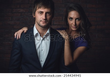 Happy young couple in love  posing next to the wall in stylish dresses. - stock photo