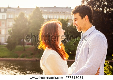 Happy young  couple in love sitting in front of each other in Strasbourg near river. Young adults tourists smiling on travel in Strasbourg in a summer walking on a date. - stock photo
