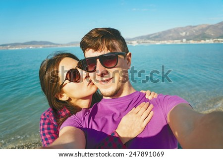 Happy young couple in love taking self-portrait on background of blue sea and woman kissing a man - stock photo
