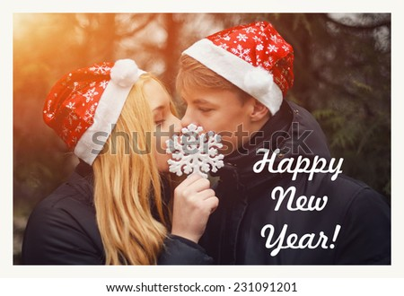 Happy young couple in love wearing Santa hats kissing and holding a big snowflake. Man and woman celebrating Christmas and New Year. Retro vintage instagram filter - stock photo