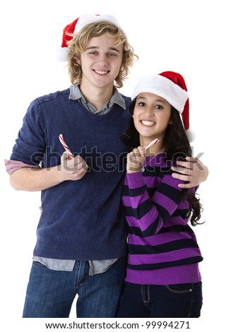 happy young couple in Santa hats holding candy canes - stock photo