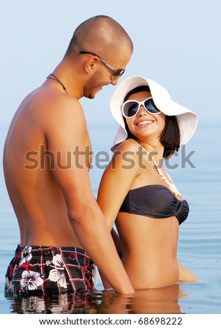Happy young couple in sea - stock photo
