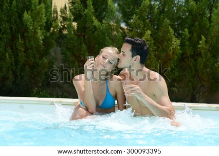 happy young couple in spa resort drinking champagne in whirlpool bath - stock photo