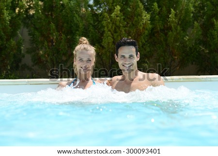happy young couple in spa resort taking whirlpool bath - stock photo