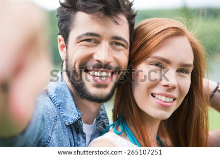 Happy young couple in summer, man pointing