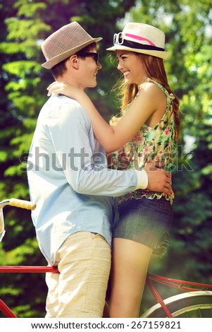 Happy young couple in summer park rides a bike. Romance and love. - stock photo