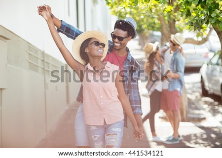 Happy young couple in sunglasses dancing on roadside - stock photo