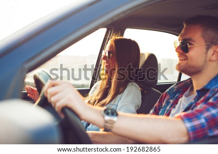 Happy young couple in the car. - stock photo
