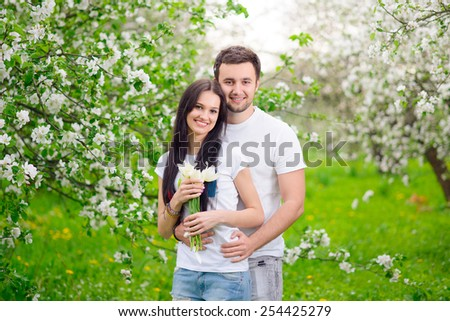 happy young couple in the garden with apple flowers - stock photo
