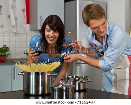 Happy young couple in the kitchen cooking dinner - stock photo