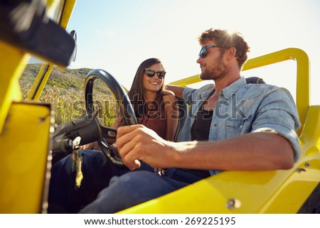 Happy young couple in their car going on a road trip. Young man driving car with woman sitting by on a summer day. - stock photo