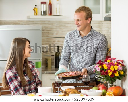 Happy young couple is having a Thanksgiving dinner at home.