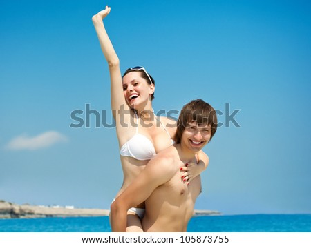Happy young couple is having fun on the beach - stock photo