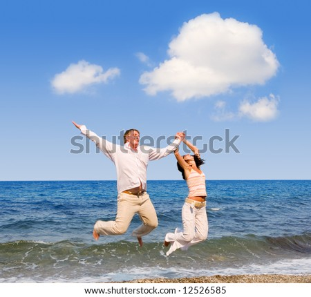 happy young couple is jumping in the beach - stock photo