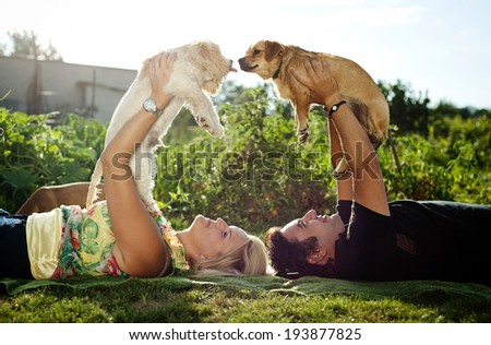 Happy young couple is laying down on grass and playing with their dogs - stock photo