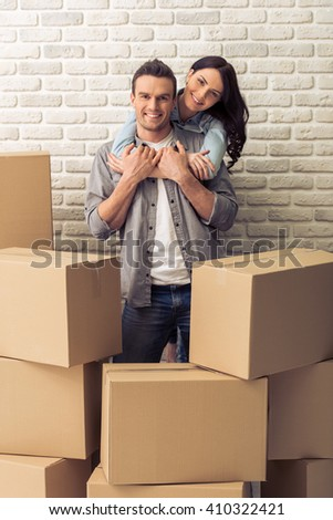 Happy young couple is moving, cuddling, looking at camera and smiling while standing among cardboard boxes. Woman is pickaback - stock photo