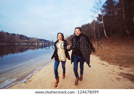 Happy, young couple is running on the beach in spring - stock photo