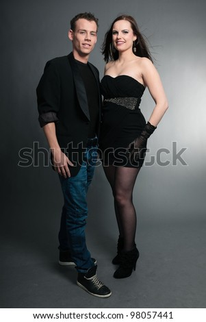 Happy young couple isolated on grey background. Fashion style studio portrait.