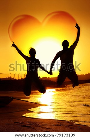 Happy young couple jumping, holding hands with heart shape in the sky, symbol of happiness, family playing outdoor, sunset on the beach, fun romantic honeymoon vacation, love concept - stock photo