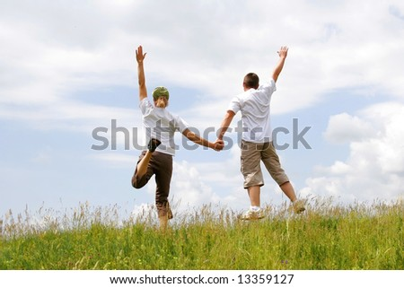 Happy young couple jumping in the sky above a green meadow