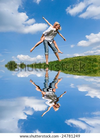 Happy Young Couple - jumping in the sky above a green meadow - stock photo