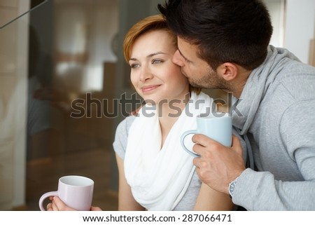 Happy young couple kissing at home, smiling. - stock photo