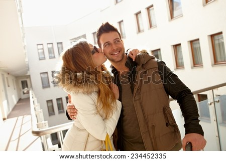 Happy young couple kissing in apartment house, smiling, embracing. - stock photo