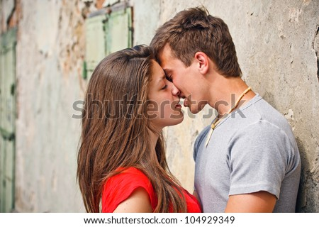 Happy young couple kissing on the city street. - stock photo