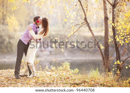 happy young couple kissing outdoor in the autumn park - stock photo