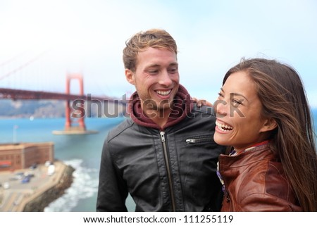 Happy young couple laughing in San Francisco by Golden Gate Bridge. Interracial young modern couple, Asian woman, Caucasian man. - stock photo