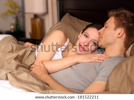 Happy young couple laying in bed - stock photo