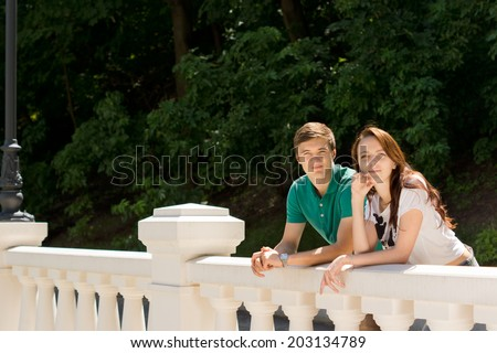 Happy young couple leaning on a white cement balustrade in front of leafy greenery as they give the camera a friendly smile, with copyspace - stock photo