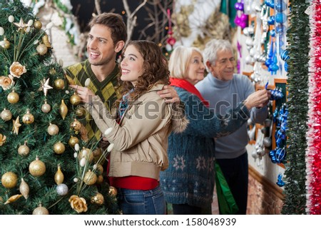 Happy young couple looking at decorated Christmas tree while parents shopping in background at store - stock photo