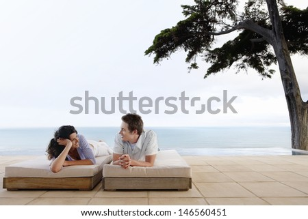 Happy young couple looking at each other while relaxing on sunbeds by infinity pool