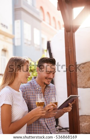 Happy young couple looking at tablet while enjoying some beers and smiling toothy smiles with bright sunshine behind them