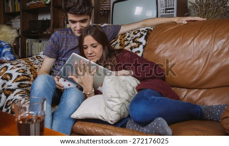 Happy young couple looking digital tablet sitting on a sofa at home