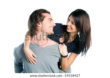 Happy young couple looking each other while piggyback with fun, isolated on white background - stock photo
