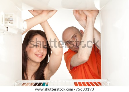 Happy young couple looking in empty refrigerator. - stock photo