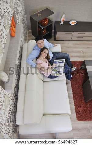happy young couple looking old pictures in photo album at home - stock photo