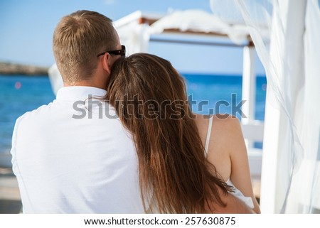 Happy young couple looking on the sea - stock photo