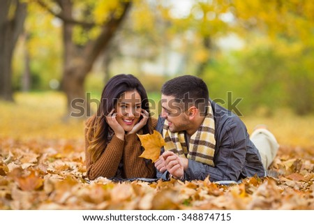 Happy young couple lying among autumn leaves in a park - stock photo